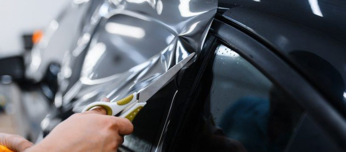 male-worker-holds-sheet-film-car-tinting-installation-tuning-service-mechanic-applying-vinyl-tint-vehicle-window-garage-tinted-automobile-glass_266732-18150